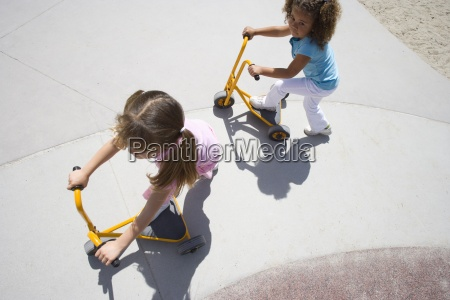 girls 4 6 playing on tricycle