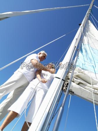 senior couple erecting sail on yacht