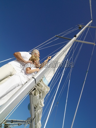 senior couple erecting sail on yacht