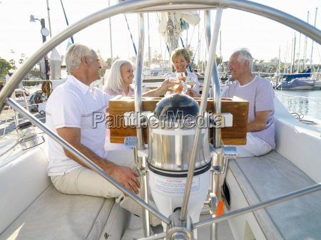 senior couple and friends on sailing