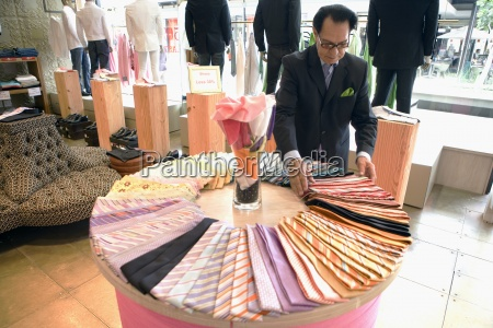 male shop assistant adjusting ties on