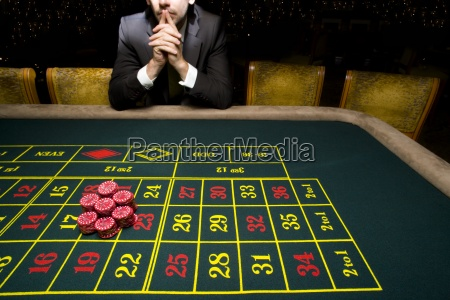 man gambling at roulette table mid