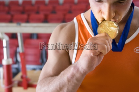 male gymnast kissing gold medal around
