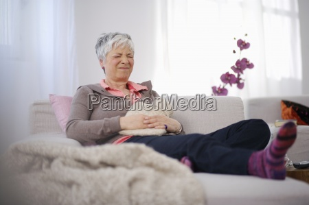 senior woman sitting on couch in