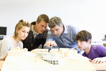 mature man and teens gathered around