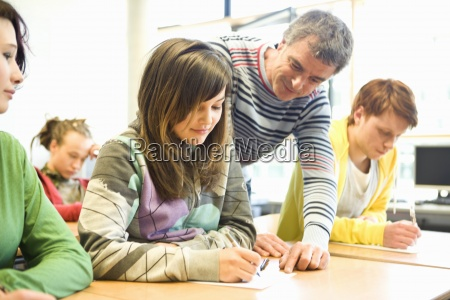 teenage students getting help from teacher