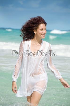 young woman walking in ocean front