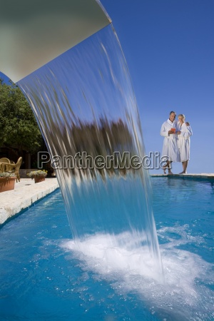 couple in bathrobes standing at edge