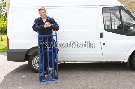 smiling man in coveralls leaning on