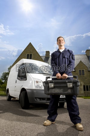 tradesman in coveralls holding toolbox near