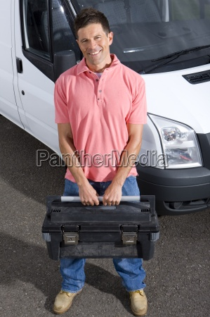 smiling tradesman holding toolbox near work