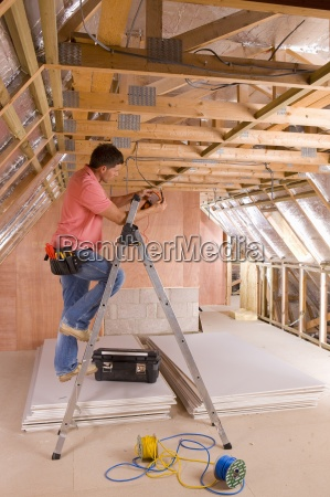 electrician using meter on ladder in