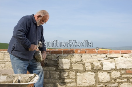 stonemason chipping at stone with mallet