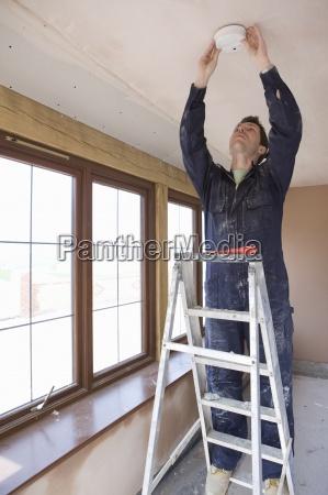 male electrician on ladder installing smoke