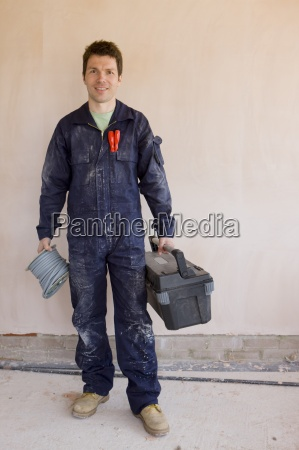 smiling electrician in coveralls holding spool
