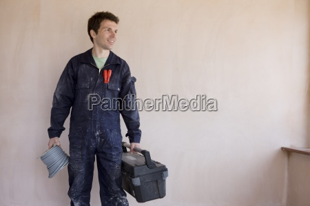 smiling man in coveralls holding spool
