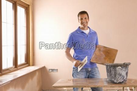 smiling man holding trowel next to