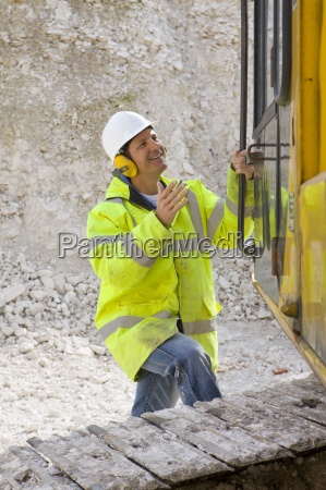 construction worker in reflective clothing climbing