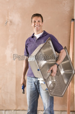smiling male plumber holding wrench and