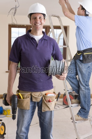 smiling electrician holding cable spool and
