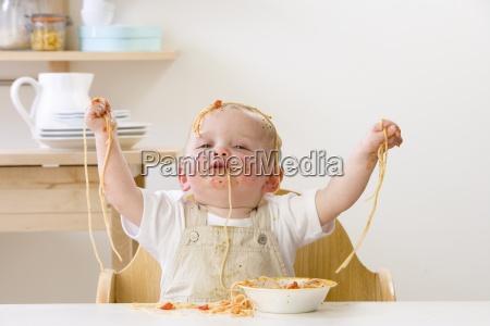 messy baby im hochstuhl isst spaghetti
