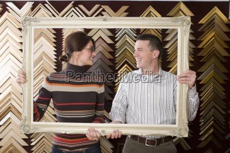 clerks lifting gold frame in frame