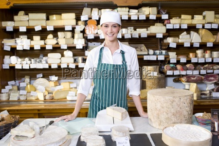 saleswoman standing at counter with cheese