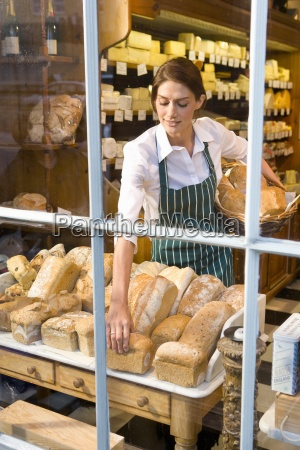saleswoman arranging fresh loaves of bread