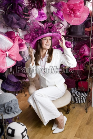 customer trying on ornate pink feathered