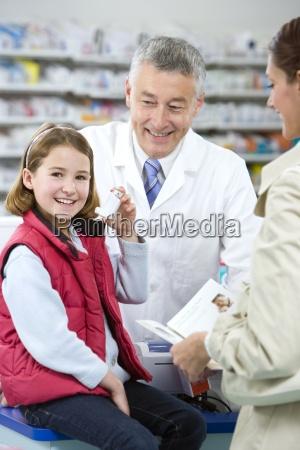 pharmacist helping girl with asthma inhaler