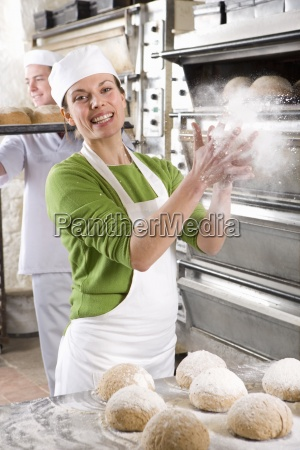 baker sprinkling bread loves with flour
