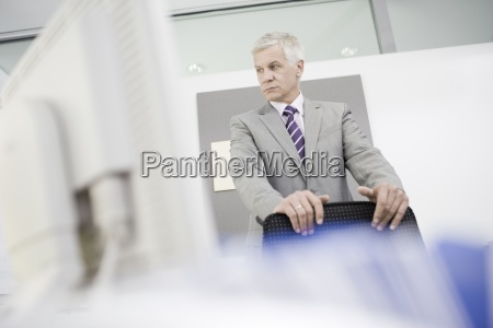 a mature businessman leaning of an