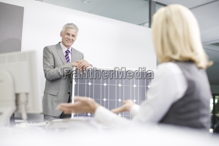two business colleagues discussing solar panel