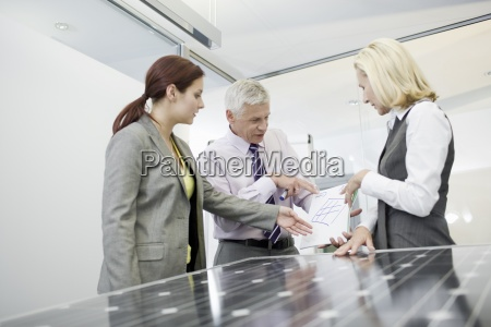 three businesspeople discussing solar panel technology