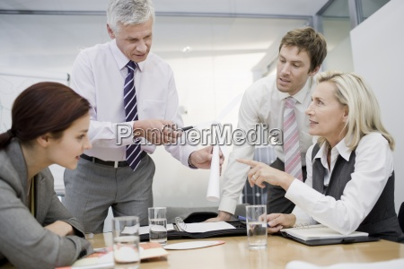four businesspeople colleagues discussing a wind