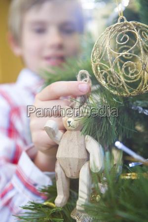boy 7 9 putting bear decoration