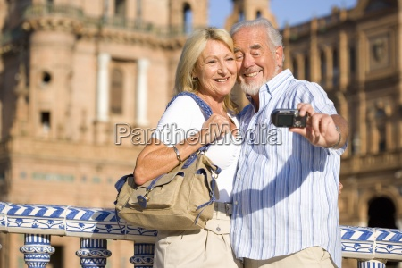 senior couple taking photograph of themselves