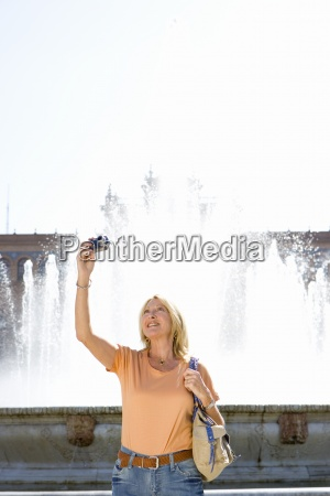 senior woman taking photograph by fountain