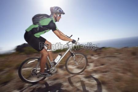 male mountain biker cycling across extreme
