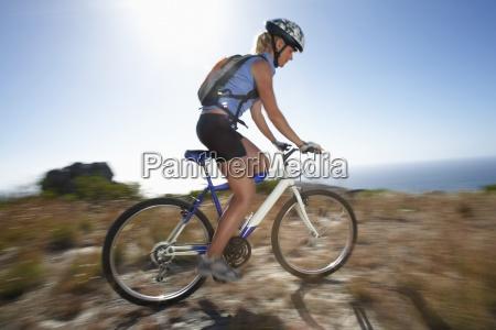 female mountain biker cycling across extreme