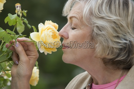 senior woman smelling yellow flower eyes