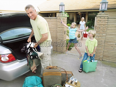 father loading car boot with luggage