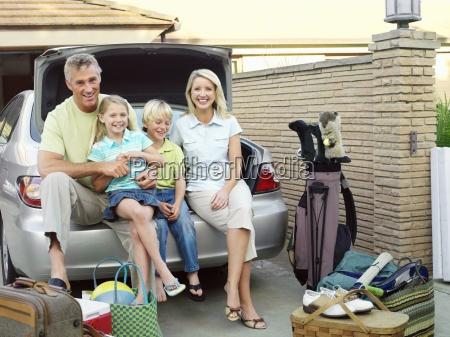 family sitting on edge of car