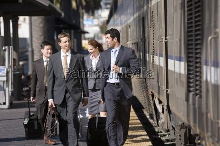 four business colleagues walking along train