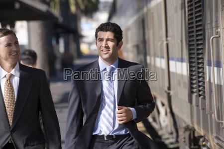 two businessmen walking along train station