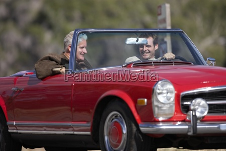 two men driving in red convertible