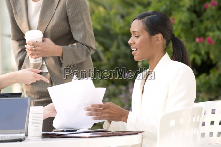 businesswoman talking to colleagues at pavement