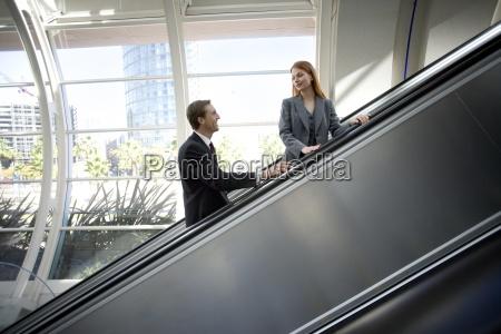 businesswoman and businessman ascending escalator smiling