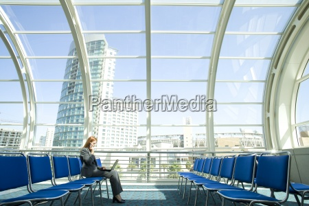 businesswoman waiting in airport departure lounge