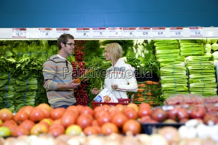 couple shopping in vegetable section of